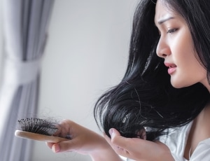 Stressed out lady looking at the hair loss on her hair brush