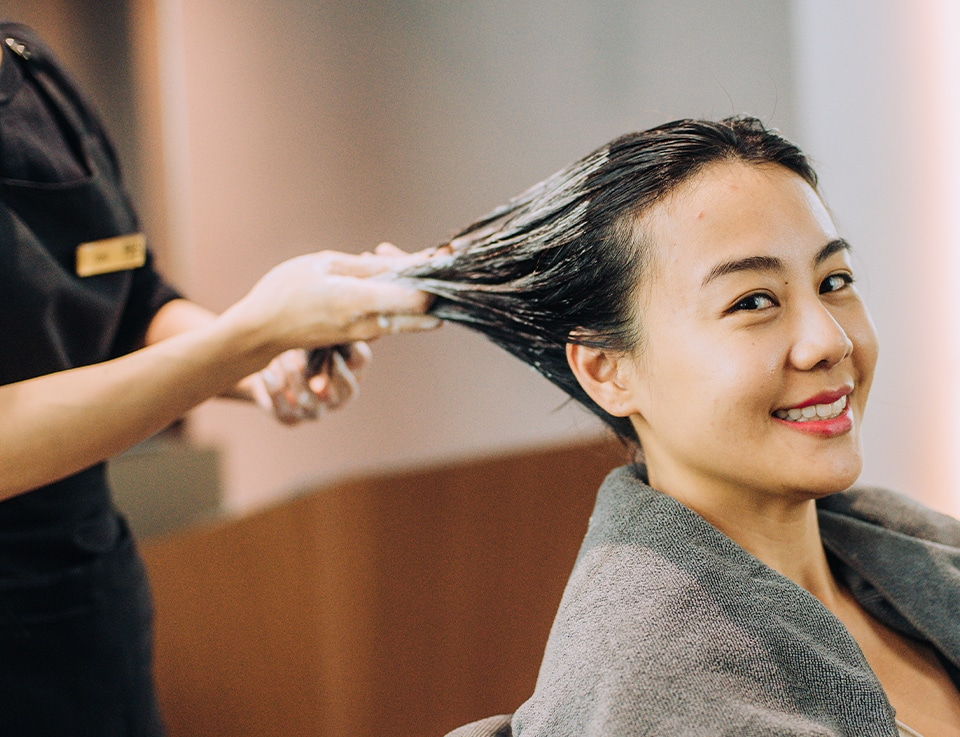 Young woman pampering herself to a hair treatment