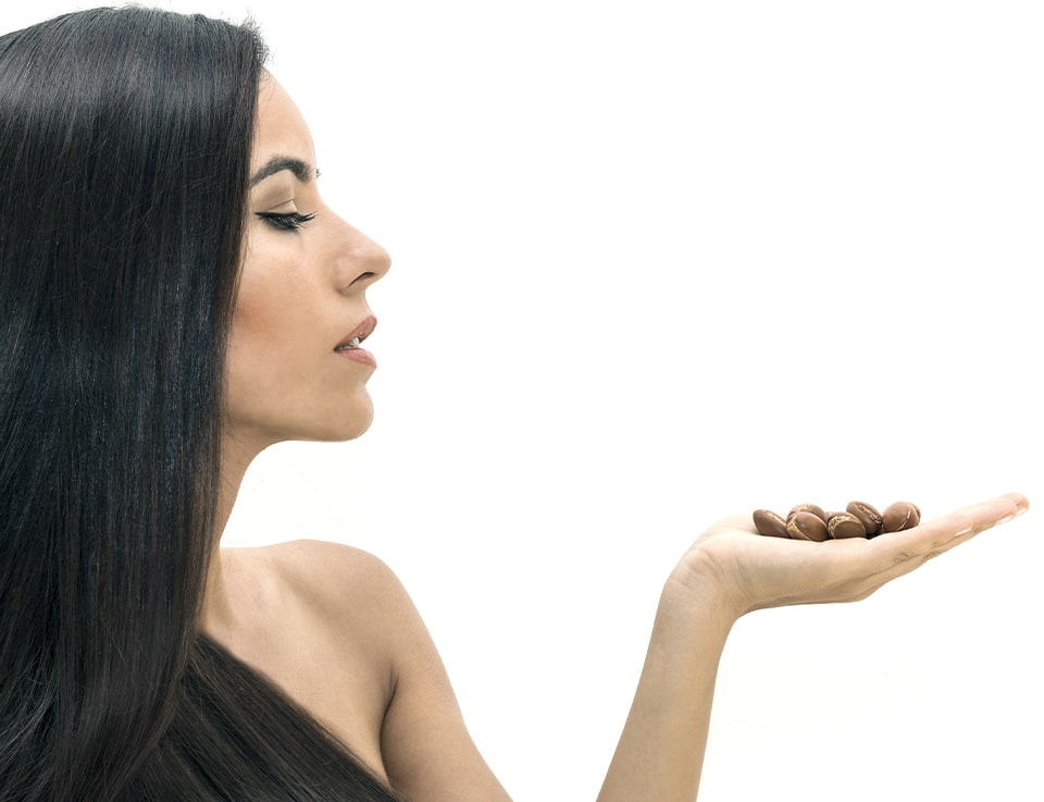 Lady with thick beautiful hair with argan nuts in palm