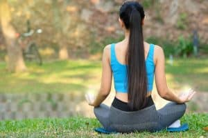Lady with long, healthy hair meditating in the forest