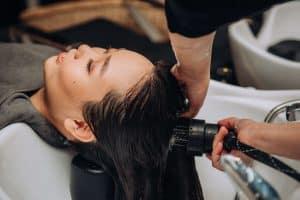 Woman enjoying a deep cleansing hair wash at phs hairscience