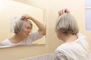 Older woman with thin gray hair and a worried look on her face examining her beginning baldness in the mirror of her yellow bathroom