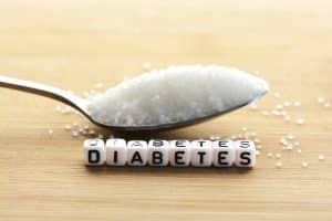 Diabetes block letters in crossword and sugar pile on a spoon