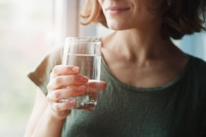 lady holding a glass of water by the window