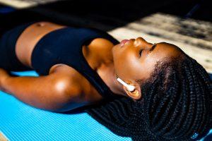woman lying down on yoga mat floor